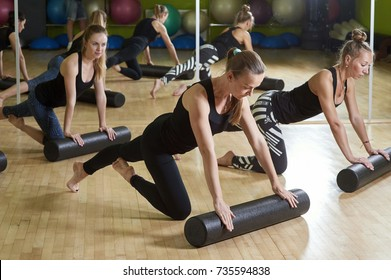 Group of women doing exercises with foam rollers in the training studio. Pilates, fitness, sport, training concept