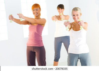 Group of women doing fitness exercise with dumbbells. They're looking at camera.