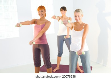 Group of women doing fitness exercise with dumbbells on mat. They're looking at camera.