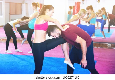 Group of women are doing kick with coach in sporty gym
