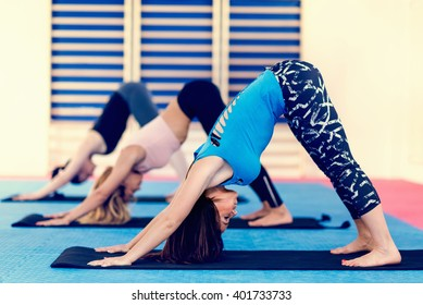 Group of women doing power y, downward facing dog