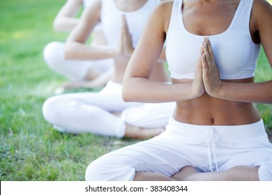 group of women doing yoga at park