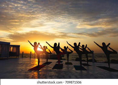 The group of women doing yoga at sunrise near the sea