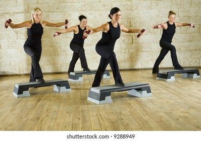 A group of women exercising with dumbbells in the fitness club. Front view.