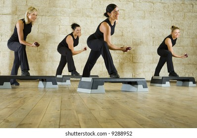 A group of women exercising with dumbbells in the fitness club. Low angle view.