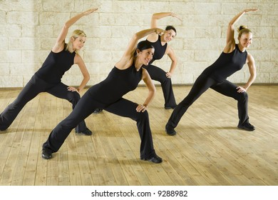 A group of women exercising in the fitness club. They're smiling. Front view.