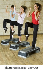 A group of women exercising in the fitness club. They're smiling and  have upraised  one leg and hands with clenched fist. Low angle view.
