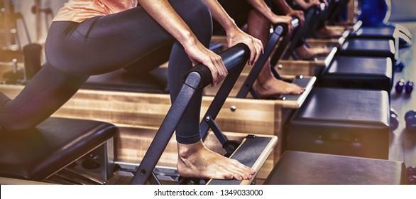 Grupo de mujeres ejerciendo sobre reformadores en el gimnasio