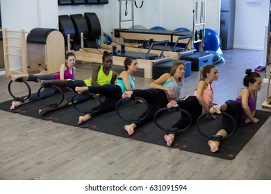 Group of women exercising with pilates ring in gym
