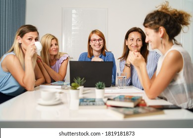 Group of women female only colleagues working together on project sitting by the desk using laptop at work in the office - Millennial boss and entrepreneurs having meeting brainstorming concept