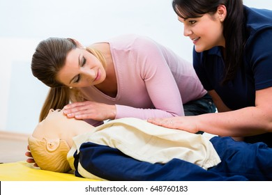 Group of women in first aid class exercising reanimation at model