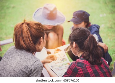 Group of Women Friends Camper Sitting in Camp Area and Reading a Guide Map Plan to Travel in Weekend - Travel and Recreation Concept