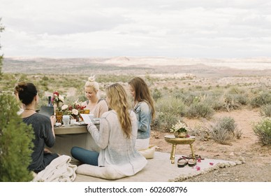 A group of women, friends sitting on the ground round a table having a meal