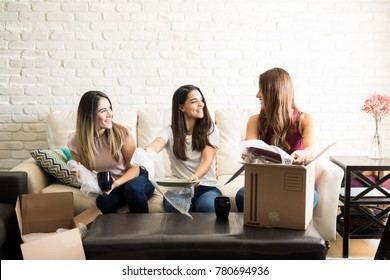 Group of women helping her new roomate unpack her stuff in their apartment