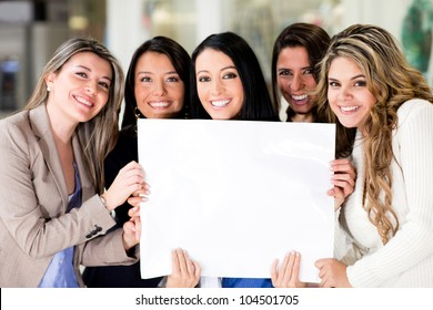 Group of women holding a banner ad and smiling