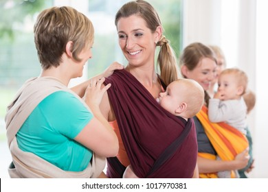 Group of women learning how to use baby slings for mother-child bonding