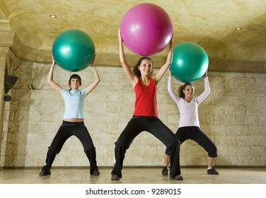 A group of women making exercise holding big balls over heads and standing astride. They're smiling. Low angle view.