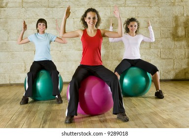 A group of women making exercise sitting on big balls with upraised hands. They're looking at camera. Front view.