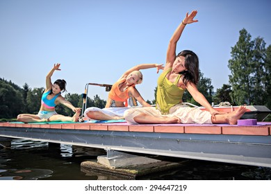 group of women making yoga exercise at a lake
