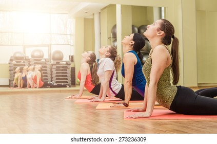 Group of women making yoga stretching in the fitness class, healthy lifestyle concept