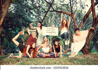 "Group of women in nature with a poster  ""Being TRANS isn't a choice, being TRANSPHOBIC is""  International Womens Day concept."