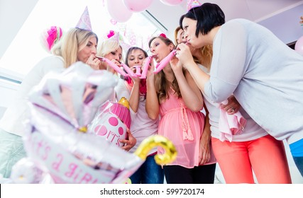 Group of women on baby shower party having fun wearing party hats blowing paper streamer
