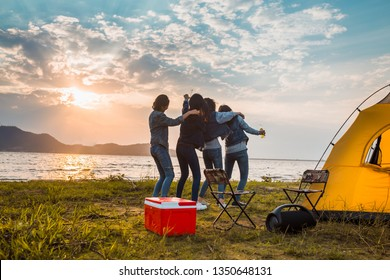 Group of women party and dancing with drink bottles enjoy travel camping,trekking in vacation time at sunset.