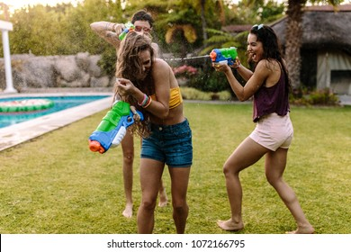 Group of women at the poolside having  water gun battle. Female friends playing with water guns.