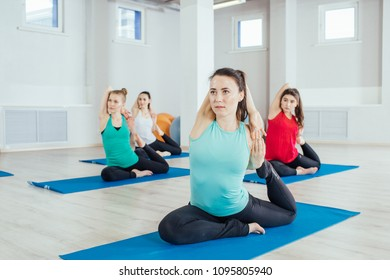 group women are practicing yoga exercises in the studio. itness, sport, people and healthy lifestyle concept