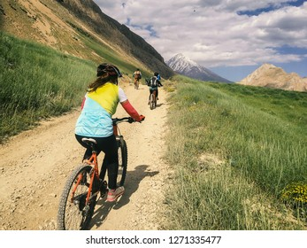 Group of women ride bicycles in a dusty road. Mountain bike. Mount Damavand in the background.