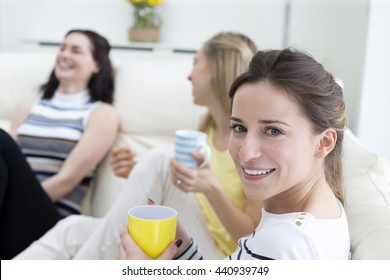 A group of women are sat at home talking and laughing. One woman is looking at the camera smiling.