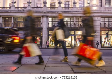 Group of  women shoppers carrying many shopping bags on city street
