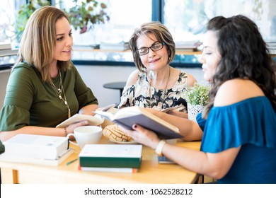 Group of women sitting around a table with lots of different books