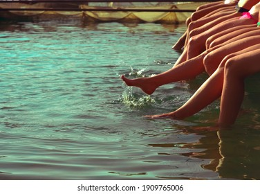 Group of women sitting in a row at the pool side. no faces. Group of girls sitting on a wooden platform by the river and splashing their feet in water on warm summer day. summertime. beach party.