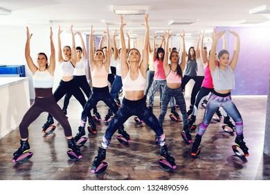 Group of women in sportswear doing exercises in kangoo jumps foot wear in fitness studio.