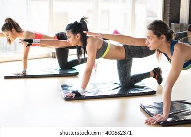 Group women stretching training exercising in gym practicing yoga pilates.