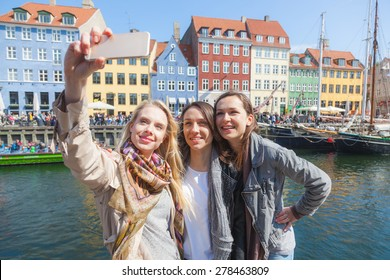 Group of women taking a selfie in Copenhagen with colourful houses on background in Nyhavn district. They are in their twenties and they are wearing smart casual clothes.