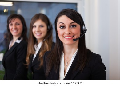 Group of women talking on the headset in their office