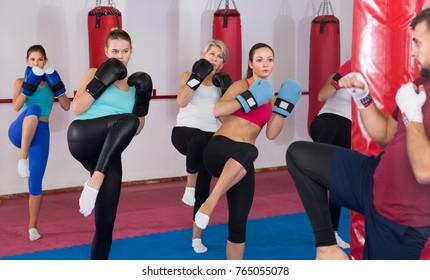 Group women and their trainer are doing kick in gym.
