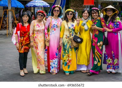 "The group of women wear traditional clothes/HoChiMinh, Vietnam – Jan 26 2017: These women wears ""Ao dai"". ""Ao dai"" is traditional clothes of Viet Nam. They were welcome a New Year, in HoChiMinh"