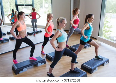 group of women working out with steppers in gym