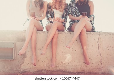 Group of women young and beautiful friends use a smartphone.. Composition with faces cutted and no visible. six legs together in friendship.