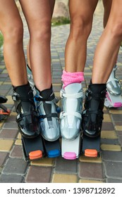 group of womens legs in kangoo jumping boots. outdoor fitness workout in group. vertical