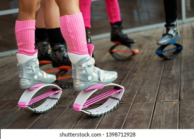 group of womens legs in kangoo jumping boots. outdoor fitness workout in group