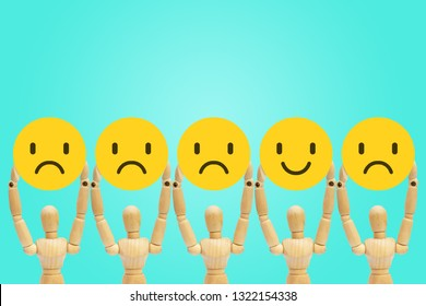 Group of wooden figure mannequin standing and holding face emotions in sadness and happiness.