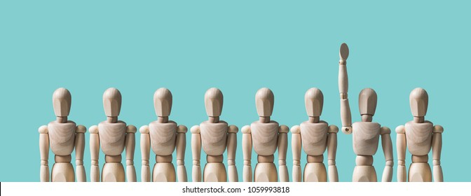 A group of wooden mannequins, one mannequin raises his hand. HR concept, human resources, volunteering. The character reports an answer, wants to apply for a job. Pastel background.