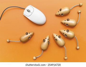 A group of wooden mouses and computer mouse on an orange background