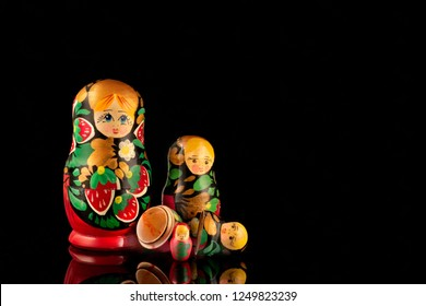 Group of wooden nesting dolls from the USSR on a black background. Traditional Russian souvenir - matryoshka (matrioshka).