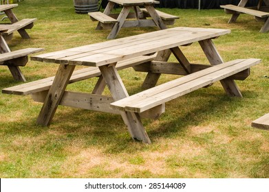 Group of wooden picnic tables in a grassy park
