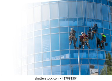 group of workers cleaning windows service on high rise building. work on the heights , industrial mountaineering. copyspase